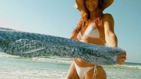 Young Caucasian woman in bikini and hat playing with scarf on beach in the sunshine 4k Live Action