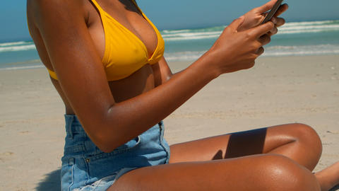 Woman using digital tablet on beach in the sunshine 4k Live Action
