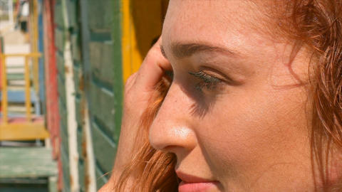 Beautiful young Caucasian woman standing on beach hut in the sunshine 4k Live Action