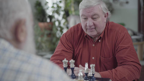 Two mature men playing chess sitting at home. Caucasian old men neighbors Footage