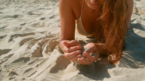 Beautiful young Caucasian woman in bikini relaxing on beach in the sunshine 4k Live Action