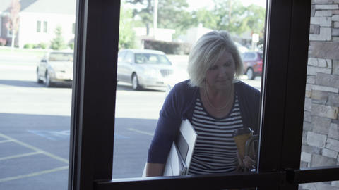 Woman, carrying coffee and large poster boards, struggles with door as another w Footage