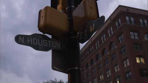 Dusk shot of the cross street sign N. Houston St. and Elm St. with the Texas Sch Footage