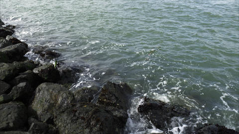 Tight shot of the waves on a rocky shore Footage