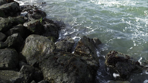 Tight shot of the waves on a rocky shore on a sunny day Footage