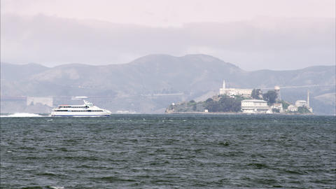 Shot following a ferry as it crosses in front of Alcatraz Island. Golden Gate Br Footage