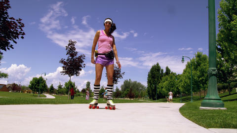 Girl dressed in 80's athletic clothing roller skating in the park Footage