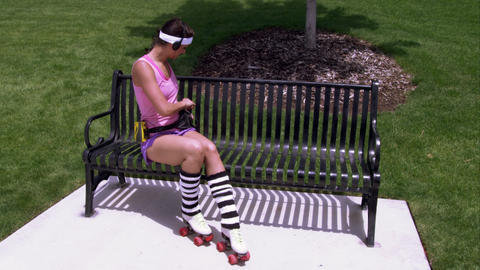 Woman dressed in 80's athletic clothing and roller skates gets up from the bench Footage
