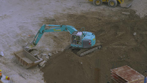 Shot from above of a trackhoe moving large chunks of concrete Footage