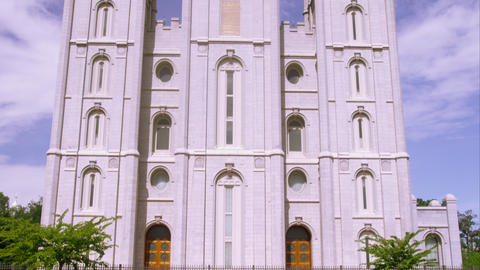 Tilting up shot of the front of the LDS Salt Lake Temple from a reflecting pool Footage