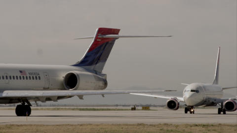 Static shot of two commercial airliners trucking on the runway Footage