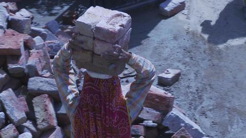 Women Laborer carrying bricks on head Footage