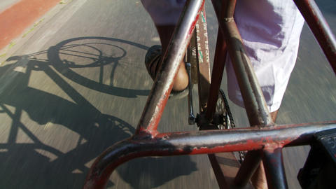 Shadow of bicycle rickshaw, feet and pedals Footage