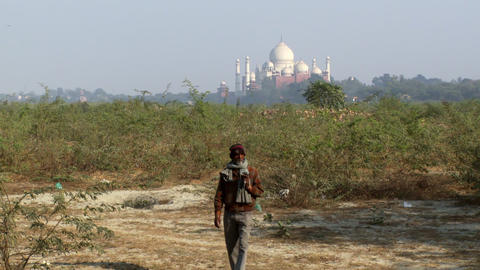 bearded man in hat and scarf walks towards camera, Taj Mahal in background Footage