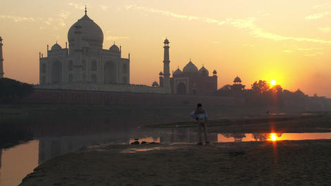 Man walking around as the sunsets behind the Taj Mahal Footage
