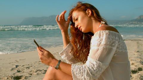 Caucasian woman using mobile phone while sitting on beach in the sunshine 4k Live Action
