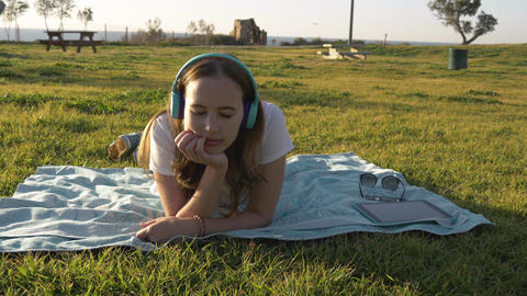 Female lay on grass in the park and listening to music in headphones Footage