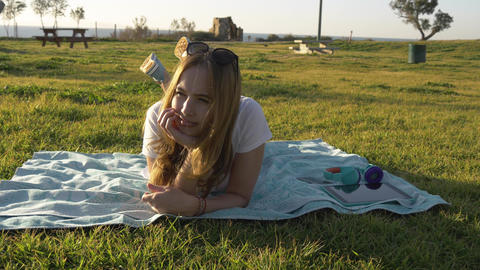 Young woman in good mood lay in the park and dreams Archivo