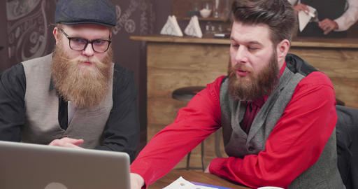 Two guys in a vintage style coffee shop greeting their colleagues in an online Footage