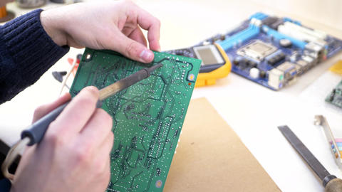 Young computer technician soldering green motherboard Live Action