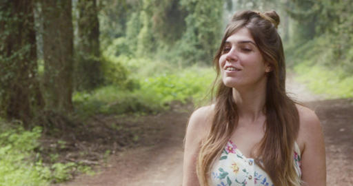Young beautiful woman with a white dress walking in a green forest Live Action