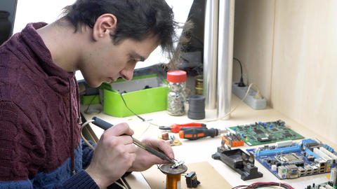 Student repair of electronic devices in electronics workshop, Live Action