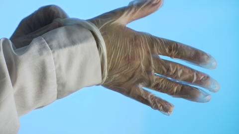 Medical doctor wearing latex blue gloves on a blue background Live Action