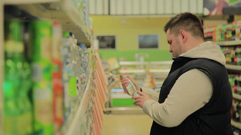 Fat man in the supermarket chooses breakfast items for himself Footage