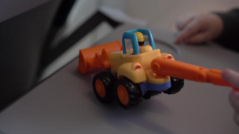 Hands of little boy play a excavator toy in the airplane GIF