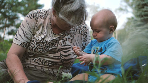 Happy kid playing with grass together with his grandmom on a lawn in slo-mo Footage