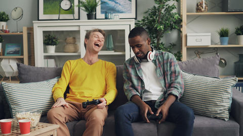 Emotional young people African American and Caucasian are playing video game at Footage