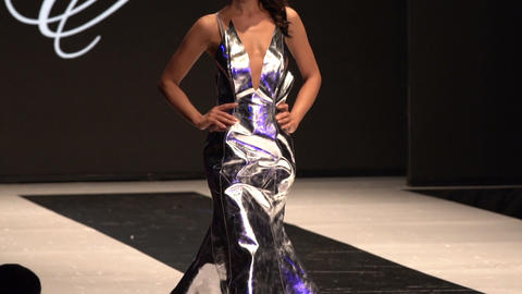 Female model walks the runway in silver dress during a Fashion Show. Fashion catwalk event showing Live Action