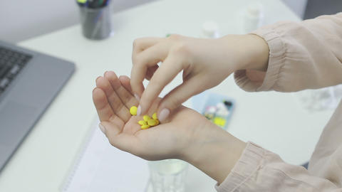 Woman pours a yellow pills out of the bottle, take one and drink water Footage