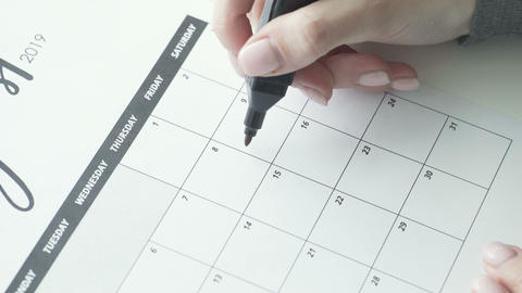 Woman's hand writing with red felt pen on calendar word party Live Action