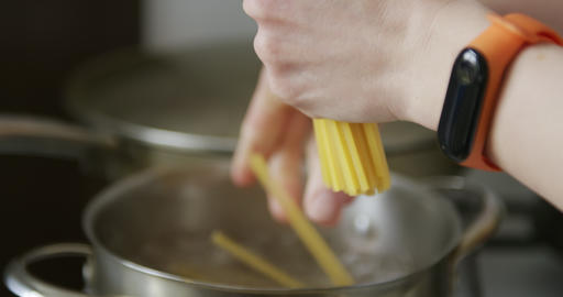 Puts pasta spaghetti in a pot of boiling water Live Action