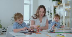 The family has fun painting on paper with their fingers in paint. Mom and two Footage