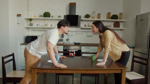 Diversing couple quarreling at kitchen table Footage