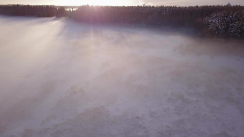 Fog hovering over frozen lake shore during sunset Live Action