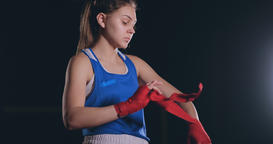 middling plan beautiful athletic boxer in blue clothes reels red bandages on the Footage