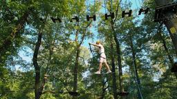 Man in Helmet in Adventure High Rope Park Doing Exercises on Single Line Bridge Footage