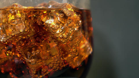 Cola in the glass with Ice cubes and bubbles rotating. Food background. Soda GIF