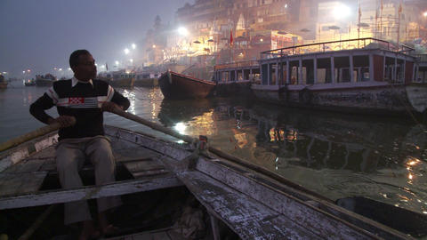 Nighttime shot of a man rowing a boat along the city shore in India Footage