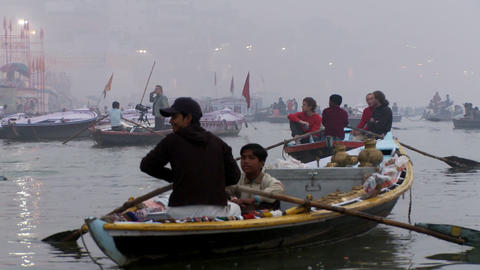 Many boats on the water rowing. City shoreline partially obscured by fog Footage