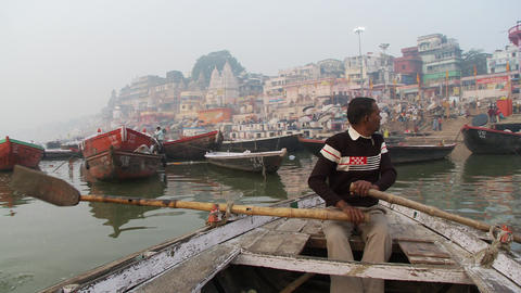 Man rowing boat toward Indian city docks Footage