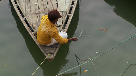 Boy fishing from bow of wooden boat from over he'd Live Action