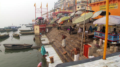 Woman and bathers on the bank of the ganges river getting dressed Footage