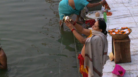Lady pouring holy water into ganges river Footage