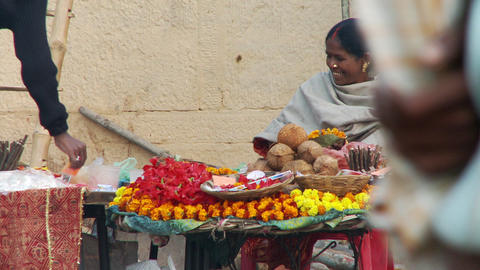 Woman in sari selling coconuts and leis on street stand Footage