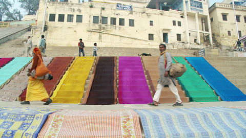 Man walking past colorful fabric on steps Footage