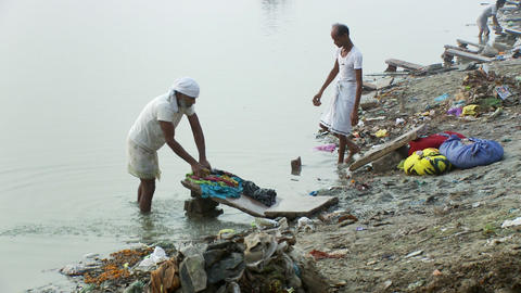 Several people washing clothes while standing in the water Footage